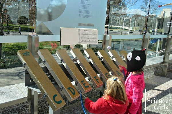 Kids playing the lithophone (stone musical instrument) outside Questacon
