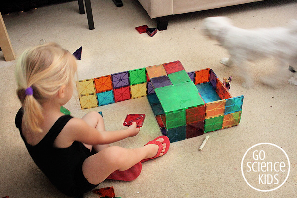 little girl playing with magna-tiles