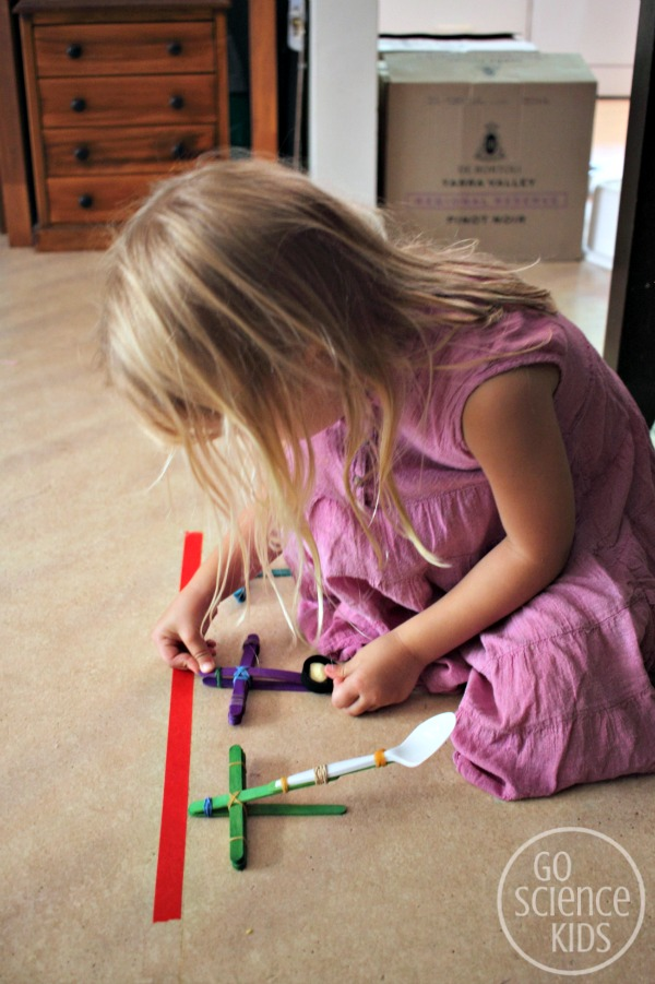 Preparing to launch her projectile with her DIY craft stick catapult